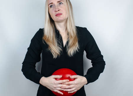Bloating and flatulence concept. The woman holds a red balloon near the abdomen, which symbolizes bloating. Intestinal tract and digestive system. Problems with flatulence and gastrointestinal tract