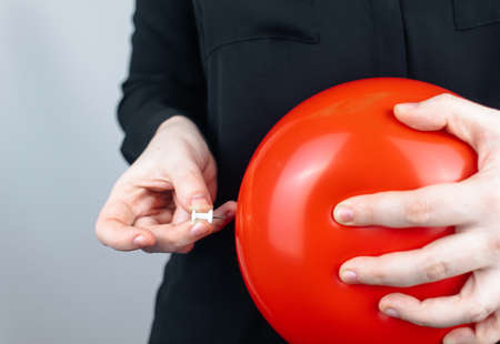 Conceptual photography. The woman holds a red ball near his belly, which symbolizes bloating and flatulence. Then she brings a needle to it to burst the balloon and thus get rid of the problem.