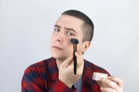 The man looks into the frame and uses powder. Close-up of a guy putting makeup on his face. LGBT community, or self-care concept. Foto de archivo