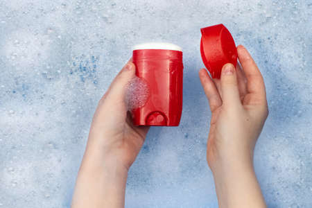 Bottles of detergents float in the foam. The concept of the dangers of household chemicals. Sodium laureate, parabens, sulfates and other hazardous chemical compounds in the foam. Dry deodorant stick