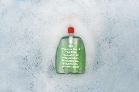 A bottle of Liquid soap floating in soapy water. Harmful composition of ingredients, detergent with SLS, Propylene Glycol, TEA, DEA, Formaldehyde, Propylparaben, Methylparaben, Butylparaben, Sodium Fluoride. The concept of hazardous substances in cosmetics and household chemicals