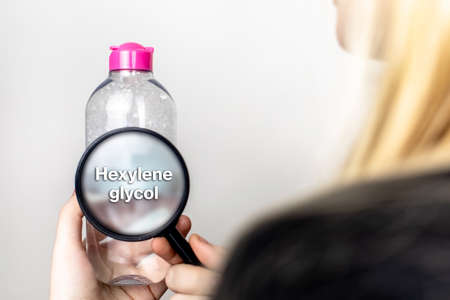 A woman examines the harmful ingredients of the micellar waterthrough a magnifying glass. Means with hexylene glycol. The concept of hazardous substances in cosmetics and household chemicals