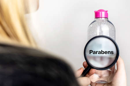 A woman examines the harmful ingredients of the micellar waterthrough a magnifying glass. Means with parabens. The concept of hazardous substances in cosmetics and household chemicals