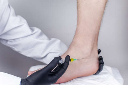 An orthopedic surgeon injects medicine into the Achilles tendon to relieve pain. Help treat sprains, trauma or injury.