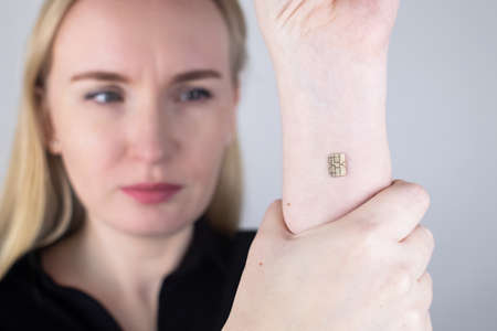 The woman shows his hand with a chip implanted. The concept of chipping and implantation of electronic technologies into the human body. Cybernetics and the nanofuture. Cyberpunk Stock Photo