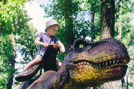 A close-up of a full-length mini Tyrannosaurus Rex. Reconstruction of extinct species. Swing for children. Styling extinct animals. Dinosaurs robots, animatronics and robotics