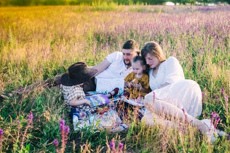 Family in the middle of a lavender field. Mom, dad and two daughters had a picnic in the steppe. Happy family in nature. Lifestyle and the concept of pleasant leisure. Sage in the sunset rays. Picnic Zdjęcie Seryjne