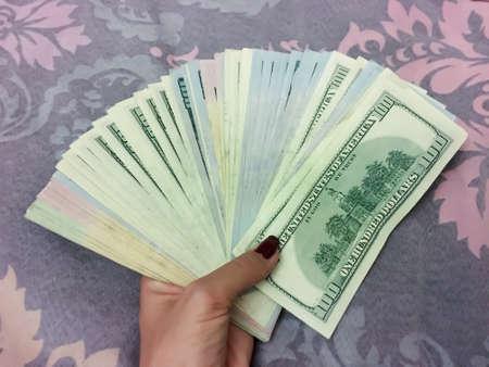 A Womans Hand Holding a lot of  100 Dollar Bills Banknotes 版權商用圖片
