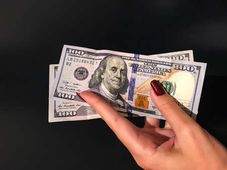 A Womans Hand Holding two 100 Dollar Bills Banknotes on a grey background 版權商用圖片
