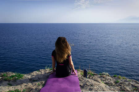 Beautiful young happy lonely girl sitting on rock and watching blue Mediterranean sea and relaxing Stock Photo