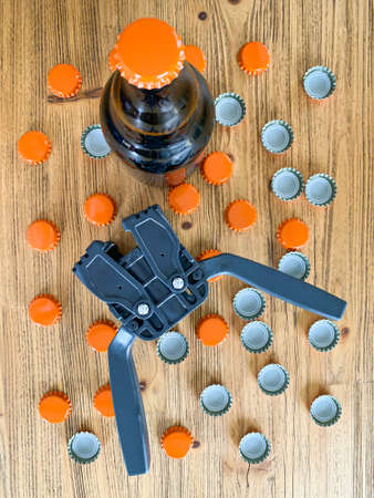 Beer brewing at home, plastic capper to put metal caps on bottles, brown glass beer bottle and orange crown caps on wooden background. Vertical image