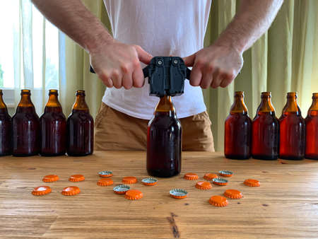 Craft beer brewing at home, man closes brown glass beer bottles with plastic capper on wooden table with orange crown caps. Horizontal image