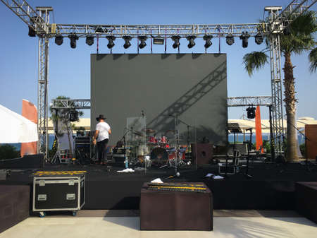 Open air show stage set up with led screen, sound and light system. Back line with drums. Horizontal image