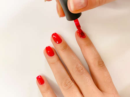 Close up female woman painting her nails with nail polish in red color on a white background. Self manicure at home Stockfoto