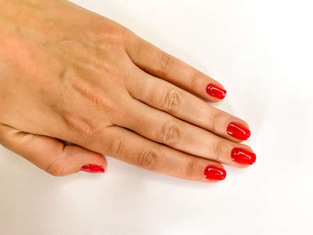 Close up female woman hand with red nails on a white background. Self manicure at home