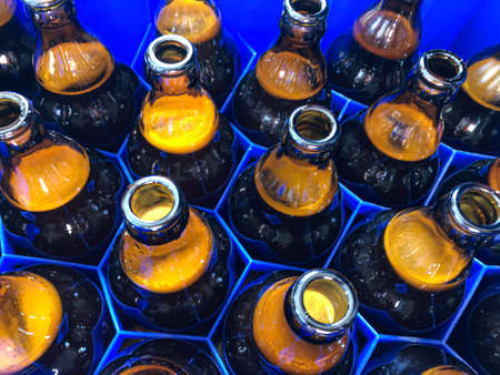 Blue plastic honeycombs shaped case with full brown glass beer bottles. Horizontal stock image