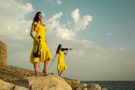 Two beautiful twin sisters violinists in yellow concert dresses are playing electric violins on rocks by the Mediterranean sea in Antalya, Turkey. Sea and cloudy sky on the background. Stock image.
