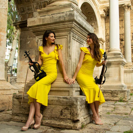 Two beautiful twin sisters violinists in yellow concert dresses are posing with electric violins near ancient Hadrian's gate in old town of Antalya Kaleici Turkey. Stock image.