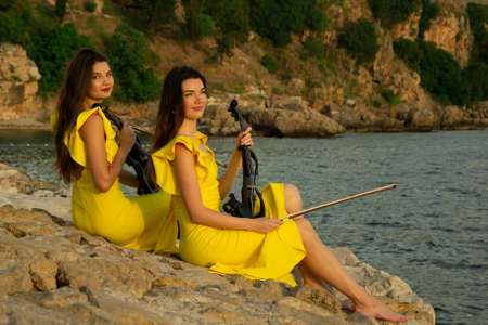 Two beautiful twin sisters violinists in yellow concert dresses are sitting on rocks by the Mediterranean sea with electric violins in old town of Antalya Kaleici Turkey. Stock image. Reklamní fotografie