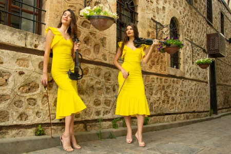 Two beautiful twin sisters violinists in yellow concert dresses are posing with electric violins near ancient stone wall in old town of Antalya Kaleici Turkey. Stock image. Reklamní fotografie