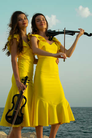Two beautiful girls violinists in yellow concert dresses are playing electric violins with sunset, mountains and Mediterranean sea on the background. Antalya Old Town Kaleici, Turkey. Stock image.