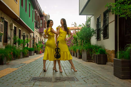 Two beautiful twin sisters violinists in yellow concert dresses are posing with electric violins on narrow Ottoman street of old town of Antalya Kaleici Turkey. Stock image.