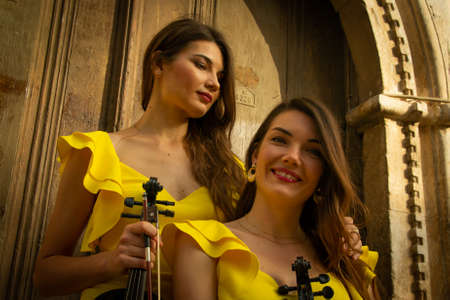 Two beautiful twin sisters violinists in yellow concert dresses are posing with electric violins near ancient wooden gate in old town of Antalya Kaleici Turkey. Stock image.