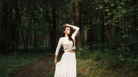 explores: Pretty woman wearing a white dress explores a beautiful forest.