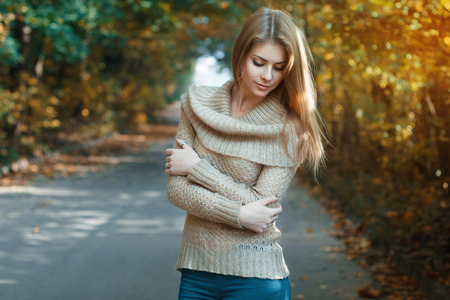 woman street: Cute woman in a jersey standing in autumn park