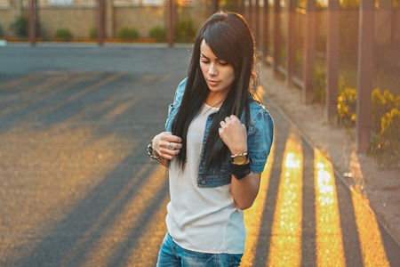 denim jacket: Beautiful girl in a denim jacket in the sunlight sunset. Stock Photo