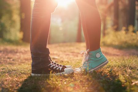 beso: Joven pareja besándose en la luz del sol de verano. Beso el amor de pie