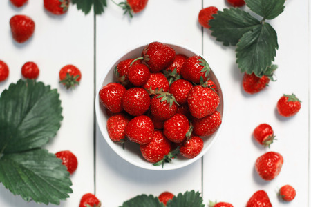 strawberry on a white wood background. selective focus on strawberries in the bowl