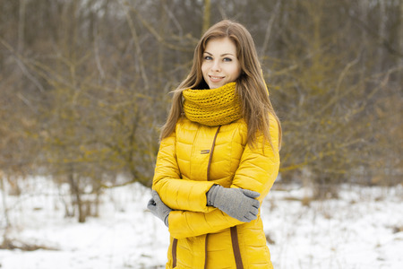 Pretty woman in a yellow knit scarf. Outdoor portrait in the park. 版權商用圖片