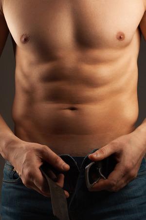 niño sin camisa: Hombre aflojar el cinturón. Músculos y el pecho abdominal. Atleta. Foto de archivo