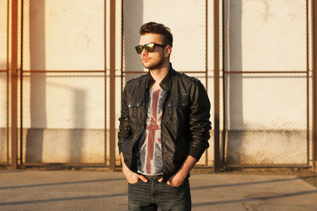 Portrait of a young man in a black leather jacket and sunglasses. Sunset on the street. Archivio Fotografico
