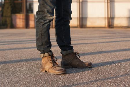 in jeans: Las piernas de los hombres con pantalones vaqueros y botas. Hipster al atardecer. Foto de archivo