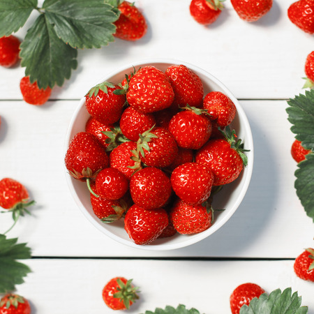 Fresh strawberries in a white porcelain bowl on wooden table in rustic style, selective focus