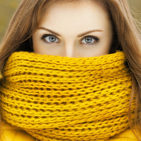 peering: Pretty woman in a yellow knit scarf looking at the camera. Beautiful eyes peering.