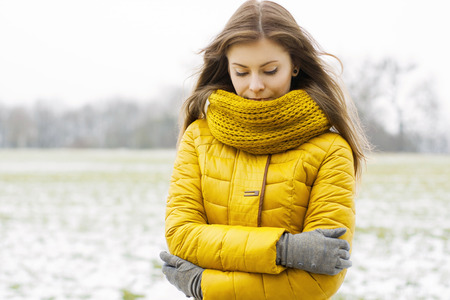Pretty woman in a yellow knit scarf and yellow jacket. Outdoors portrait in the park.