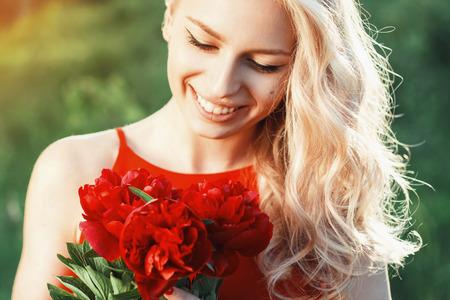 cara sonriente: Close-up retrato de la moda hermosa mujer sonriente con flores rojas.