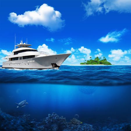 tropical beach: White yacht in the sea. Island with palm trees on the horizon. Turtle under water. Stock Photo