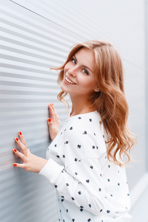 Positive beautiful woman with red nails posing near the white walls.