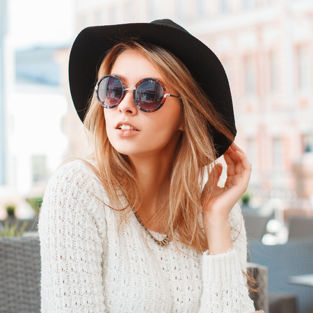 Pretty Fashionable woman with black hat and round sunglasses in cafe. Banque d'images