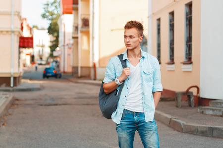 styles: Young handsome man with a backpack in a denim shirt and jeans clothes traveling.
