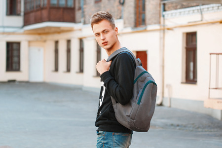 shirt: Young man with a backpack is traveling around the city. Stock Photo
