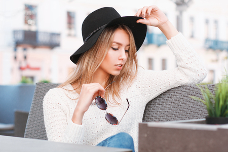 Beautiful stylish girl in a hat and sunglasses resting on a sunny day in a cafe