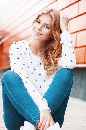 Beautiful portrait of a pretty smiling girl near stylish orange metal wall. Banque d'images