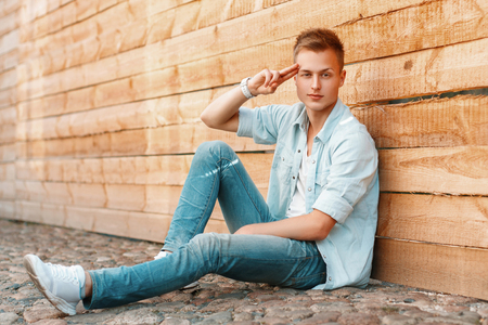 Young man posing by the wooden wall. Guy saluting.