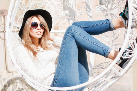 fashion sunglasses: Beautiful young girl resting in a suspended white chair.