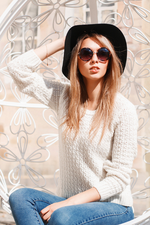anteojos de sol: Mujer bonita en un sombrero y gafas de sol descansando en un día soleado en una silla suspendida blanco